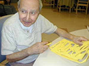 Martin Avadian trying to solve a puzzle in the activity room of a nursing home.