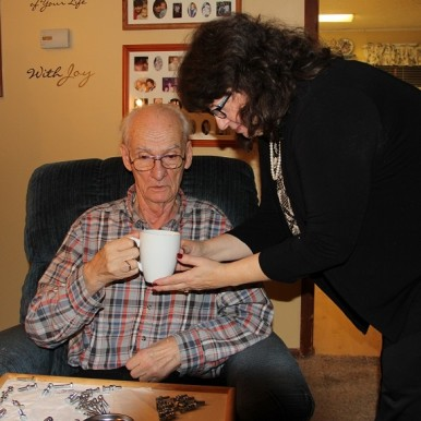 Caregiver Sheri Zschocher helping husband Bob with coffee