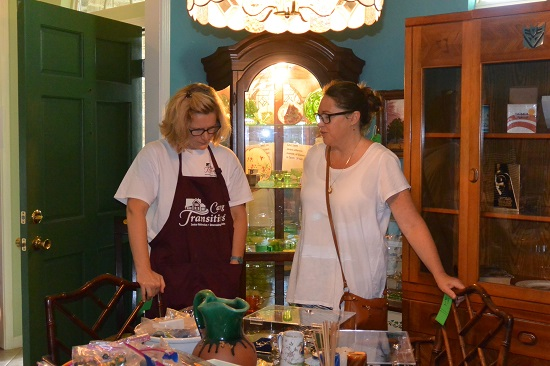 Caring Transitions owner consults with estate sale shopper on value of items