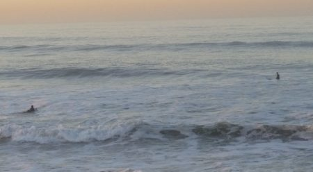 Two surfers at dawn in the Pacific Ocean