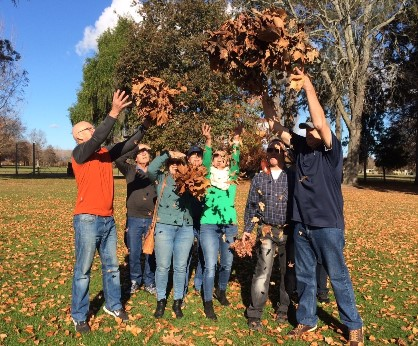 Participants in the Mahana Club - Dementia Hawkes Bay tossing Autumn leaves in the air